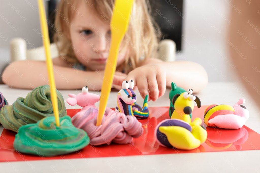 Blonde girl playing with a clay. Educating