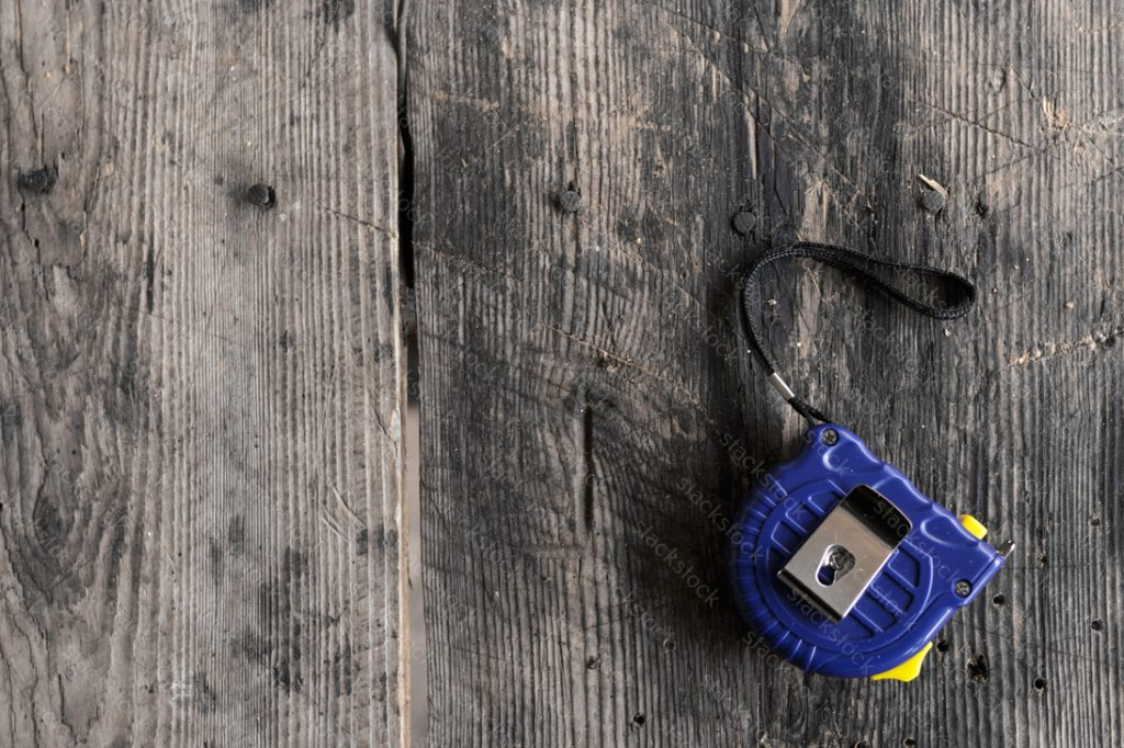Blue measuring tape on wood background