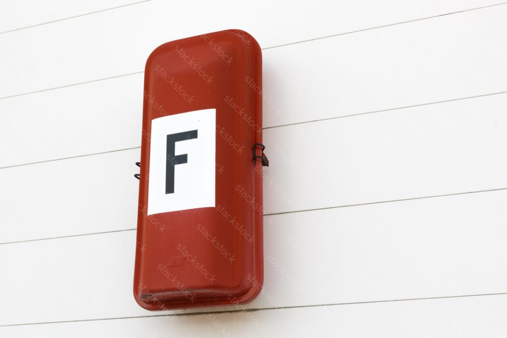 Red Fire extinguisher on the white wall