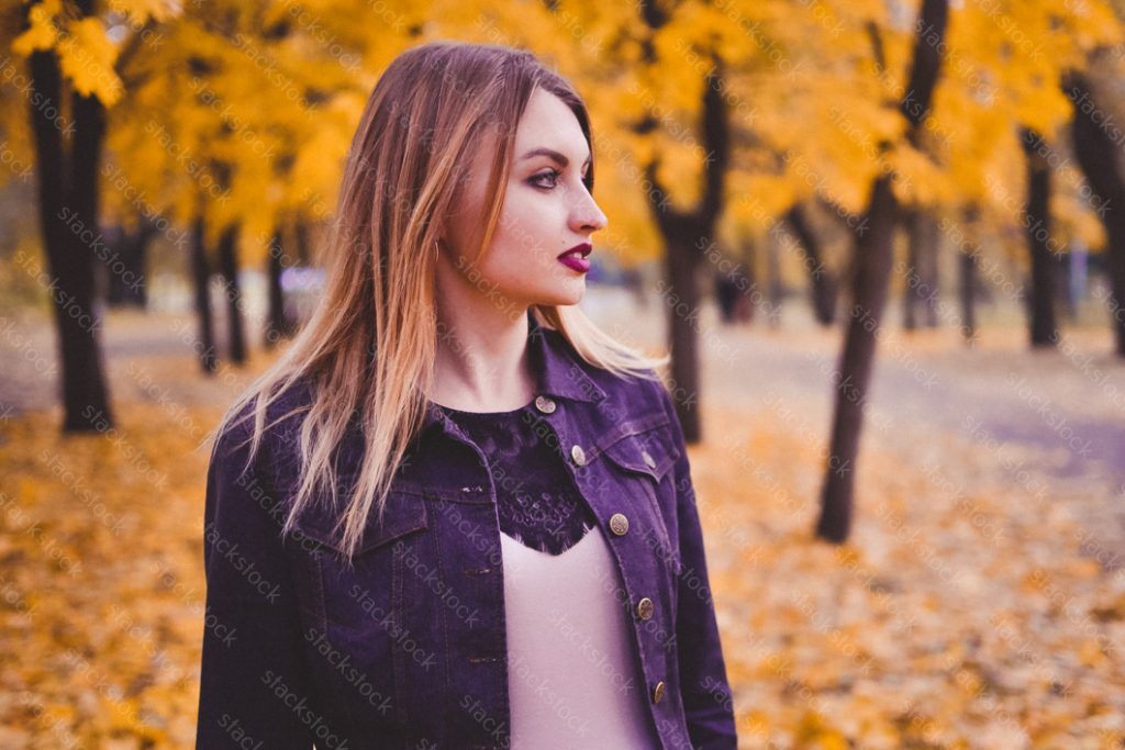 Woman in autumn in city park, outdoor portrait.