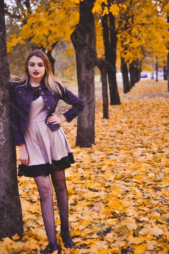 Woman posing during autumn in city park, outdoor portrait.