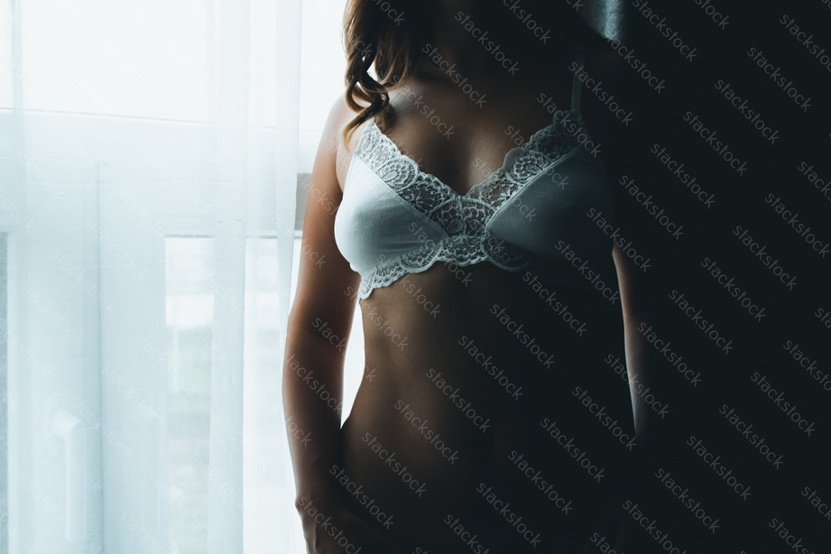 Pretty young woman standing by the window