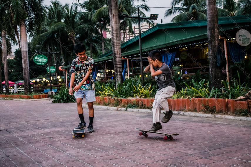 Two Filipino teen skateboarding