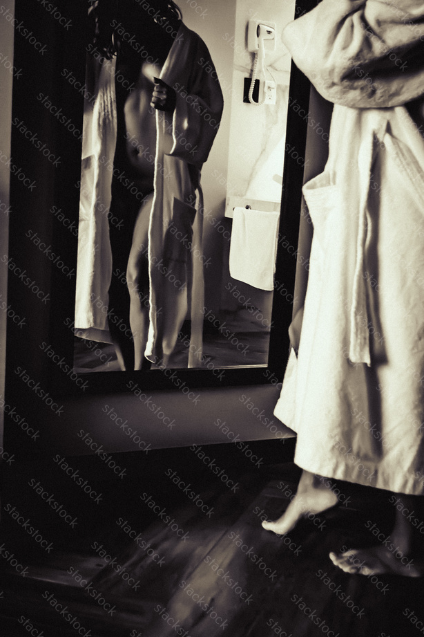 Woman wearing a robe in front of a mirror