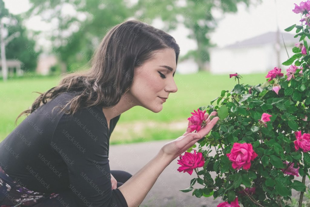 Pretty woman smelling roses