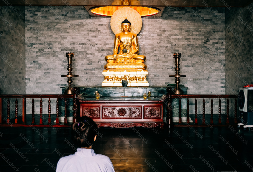 Asian woman praying to Buddha