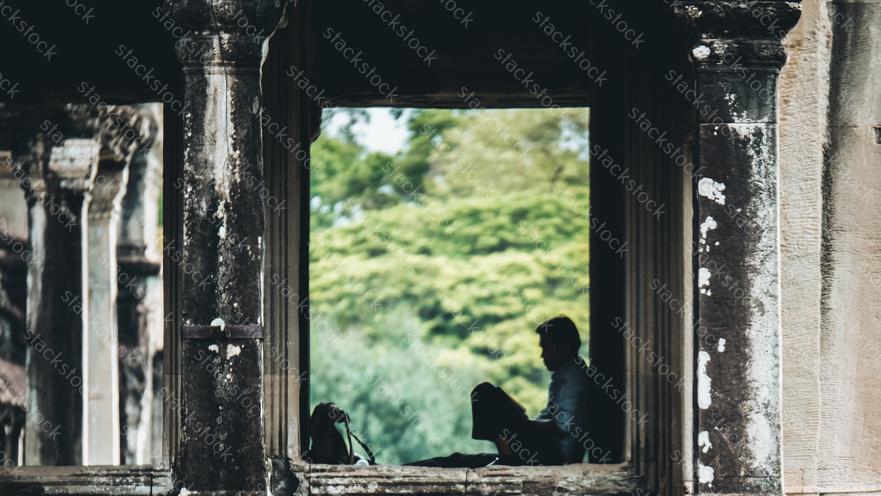 Man resting in the ruins at Angkor Wat temple, Siem Reap, Cambodia.