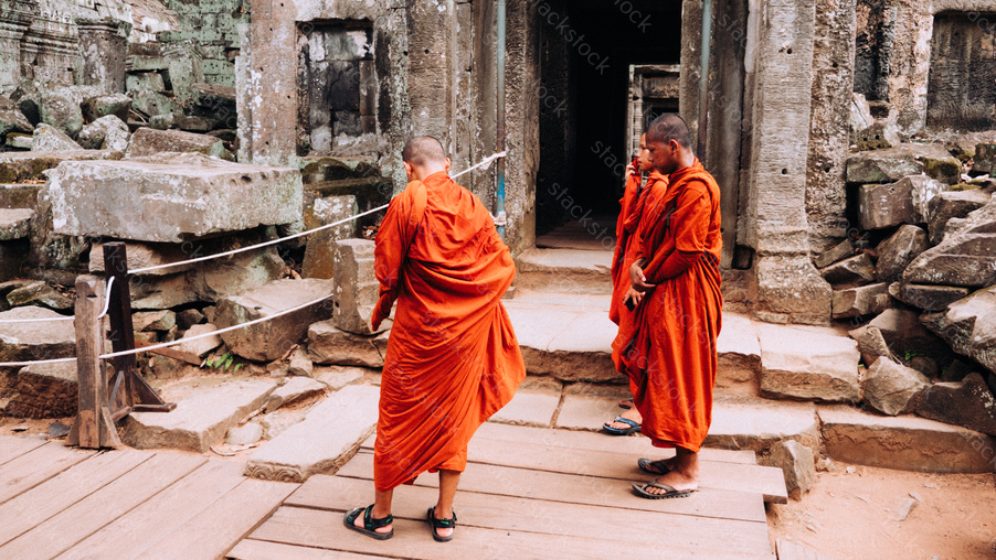 Monks visiting on walking Ta Prohm temple at Angkor Wat complex, Siem Reap, Cambodia